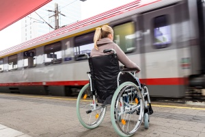 Eine junge Frau sitzt in einem Rollstuhl auf einem Bahnhof